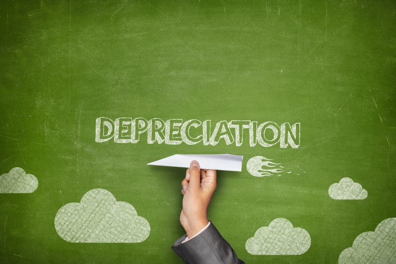 Depreciation concept on green blackboard with businessman hand holding paper plane